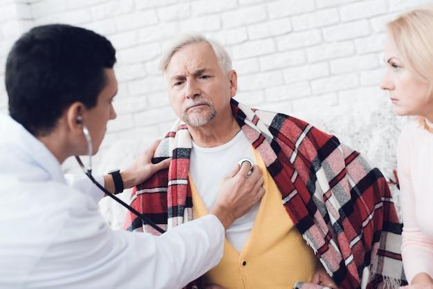 Um médico veio ao velho em um cardigan amarelo