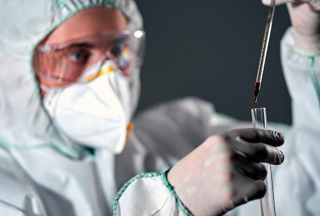 Um médico vestindo roupa de proteção, respirador e óculos segura um tubo de ensaio com sangue e um conta-gotas isolado no preto.