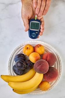 Um medidor de glicose no sangue nas mãos de um homem e um prato de frutas em uma mesa de luz