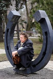 Um mendigo sentado em uma grande ferradura