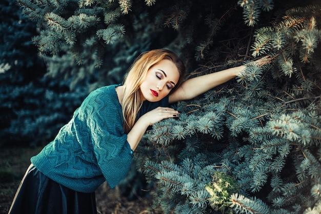 Um, menina, com, cabelo loiro, e, olhos azuis, em, um, suéter verde, em, um, parque, perto, a, azul verde, árvore abeto