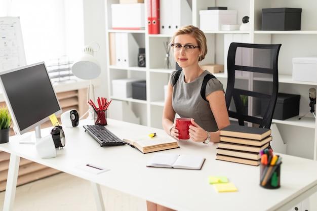 Um, menina jovem, senta-se, em, um, tabela, em, escritório, e, segura, um, copo vermelho, em, dela, mãos