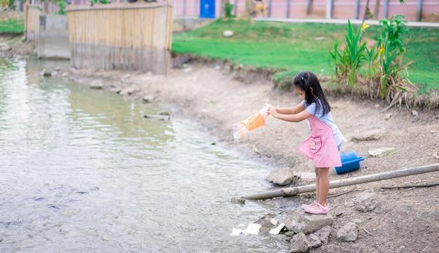 Um, menininha, alimentação, peixe, em, a, lagoa, em, parque público