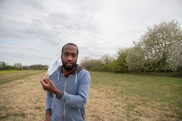 Um menino africano remove sua máscara protetora contra o coronavírus em um prado ao ar livre