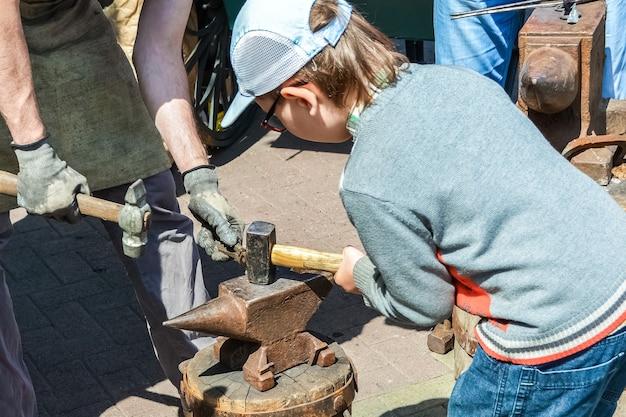 Um menino ajuda um ferreiro a fazer uma ferradura