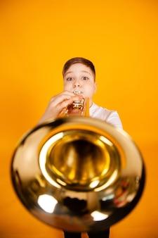 Um menino alegre toca cachimbo soprando humor nas bochechas tocando um instrumento de sopro