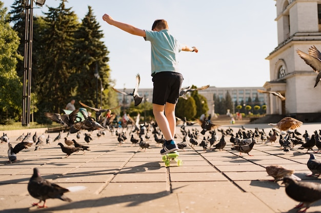 Um menino andando de moeda de um centavo no parque em um horário quente de verão com pombos e céu