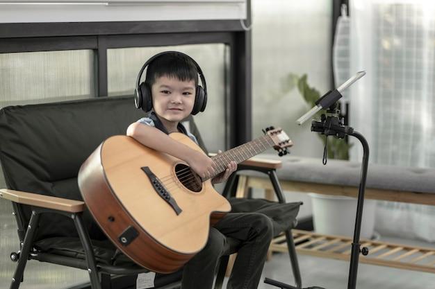 Um menino aprendendo a tocar violão, concentração em tocar a música, menino praticando um novo som no violão em casa, menino se divertindo fazendo música com violão e cantando junto em casa.