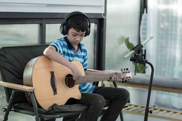 Um menino aprendendo a tocar violão concentração em tocar a música