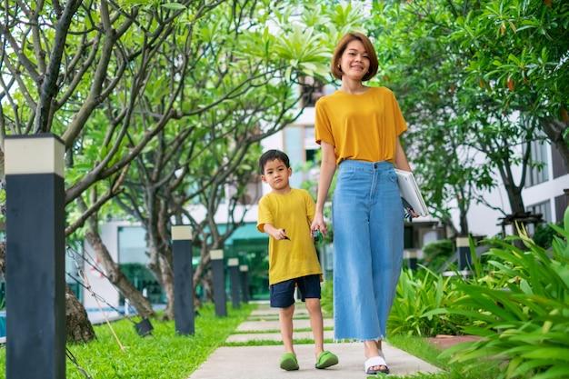 Um menino asiático com sua mãe caminha no jardim