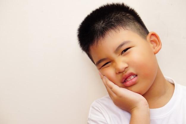 Um menino asiático com uma camiseta branca usa as mãos para segurar o rosto