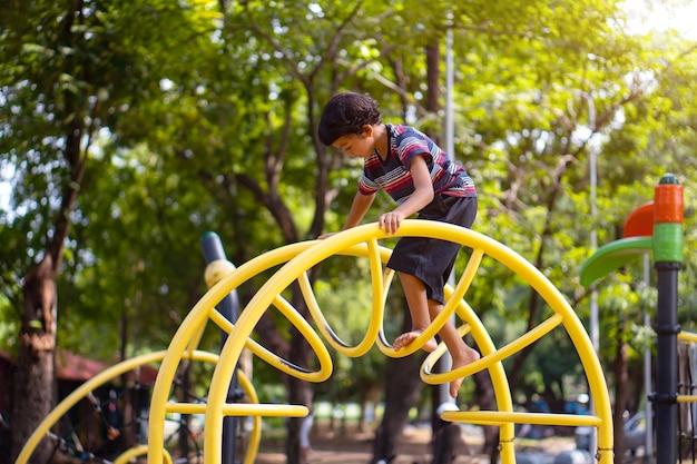 Um menino asiático está escalando em um equipamento de playground em uma escola.
