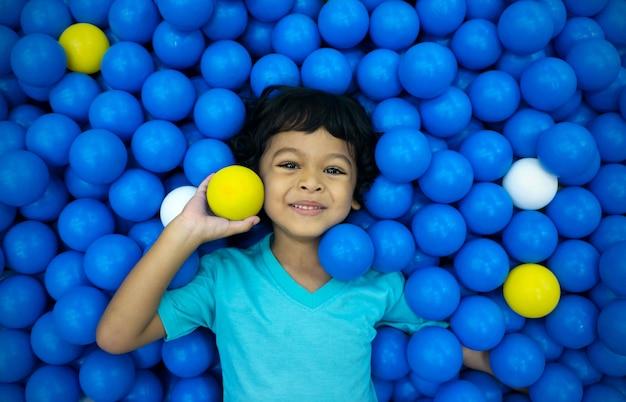 Um menino asiático está jogando com um monte de bolas azuis e amarelas