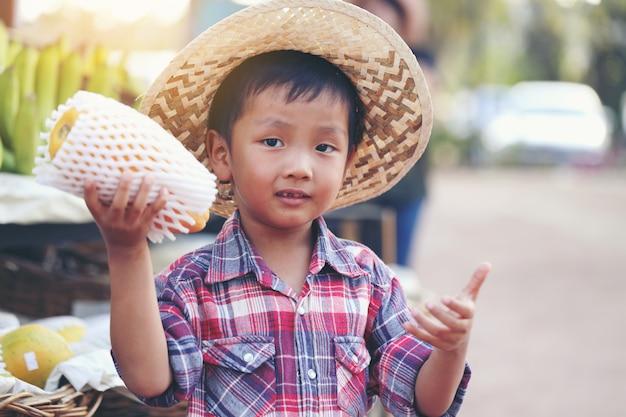 Um menino asiático mantém mamão esperando os clientes comprarem.