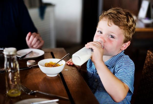 Um menino bebendo um leite