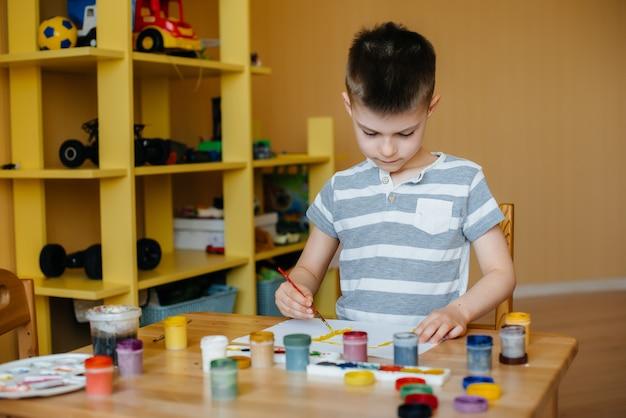 Um menino bonitinho está brincando e pintando no quarto dele. recreação e entretenimento. ficar em casa.