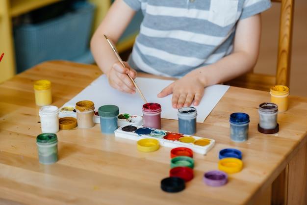 Um menino bonitinho está brincando e pintando no quarto dele.