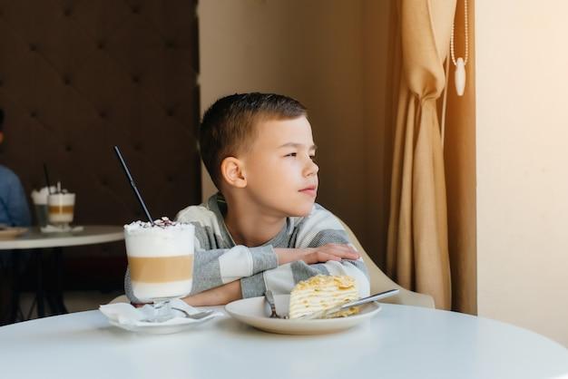 Um menino bonitinho está sentado em um café e olhando para um bolo e cacau close-up. dieta e nutrição adequada.