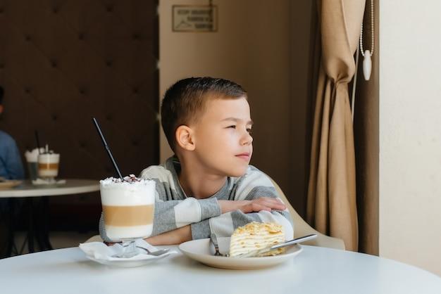 Um menino bonitinho está sentado em um café e olhando para um bolo e um close-up de chocolate. dieta e nutrição adequada.