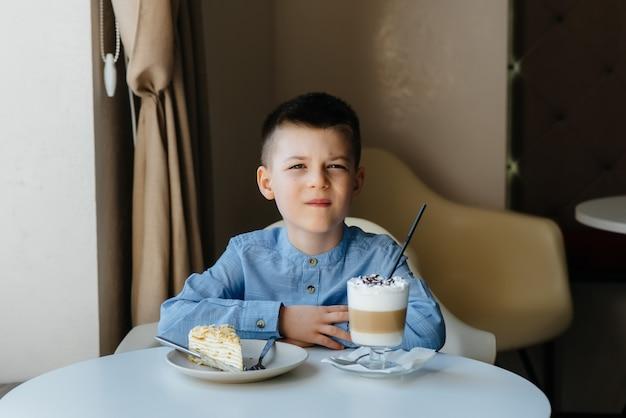 Um menino bonitinho está sentado em um café e olhando para um close de bolo e cacau. dieta e nutrição adequada.
