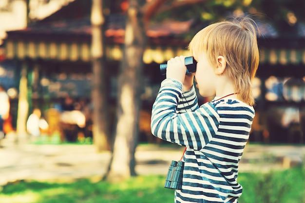 Um menino bonitinho olhando através dos binóculos ao ar livre.