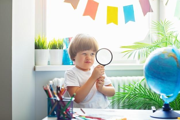 Um menino bonito em uma camiseta branca está sentado em uma mesa da escola, segurando uma lupa e olhando o globo através dela