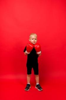 Um menino boxeador de pé em luvas de boxe vermelho