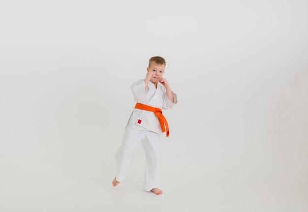 Um menino boxeador em um quimono branco com uma faixa laranja em um fundo branco