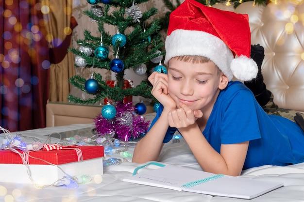 Um menino branco com um chapéu de papai noel vermelho está sonhando com presentes e surge com uma carta para o papai noel em casa decorada para o natal. tradições em torno dos feriados de ano novo e natal