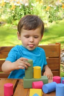 Um menino brinca com entusiasmo com cubos coloridos.