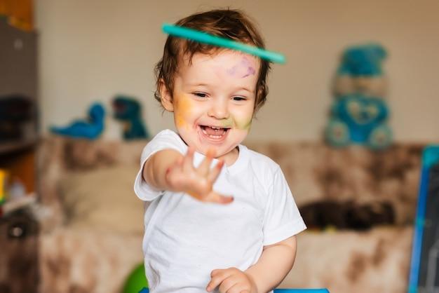 Um menino brinca com marcadores coloridos em um pedaço de papel Foto Premium