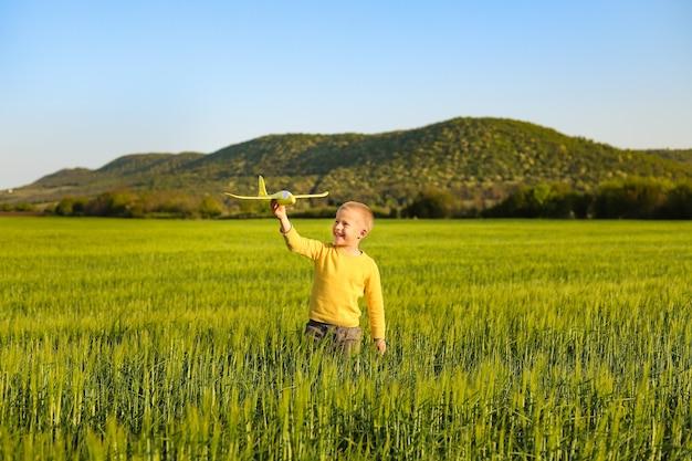 Um menino brinca com um avião de brinquedo amarelo em um campo de trigo verde.