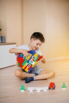 Um menino brinca com um kit de construção e constrói uma casa-grande para toda a família. construção de uma casa de família. Foto Premium