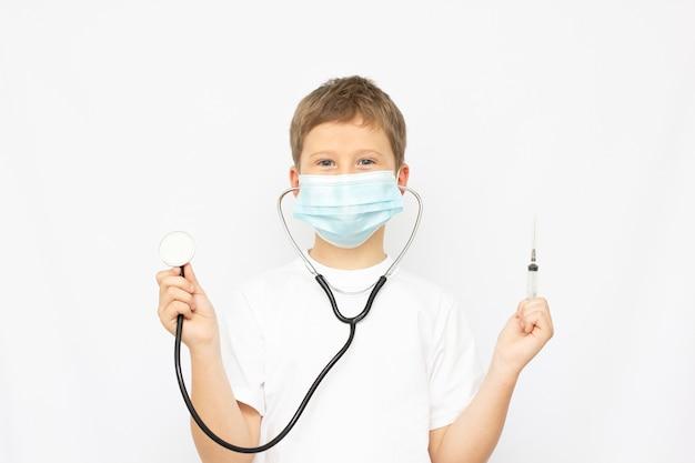 Um menino brinca de médico, um conceito de escolher uma profissão para uma criança, um menino loiro com uma camisa branca, usando uma máscara protetora e um estetoscópio