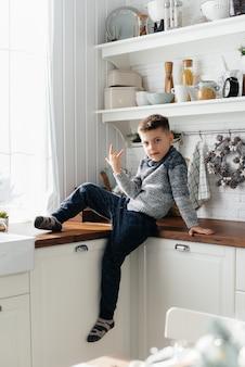 Um menino brinca na cozinha. felicidade. uma família.