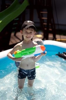 Um menino brinca na piscina com uma pistola de água. é um dia muito ensolarado