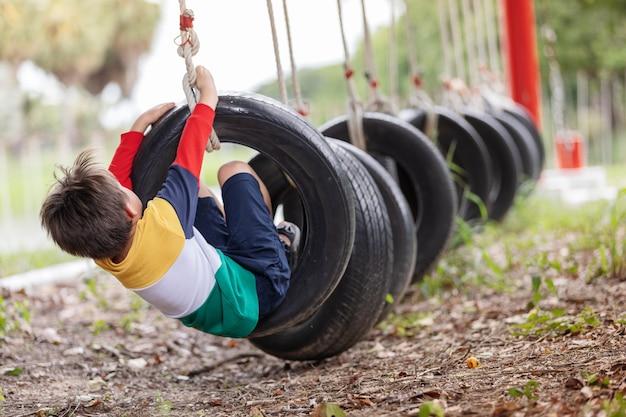 Um menino brincando de balanço de pneu pendurado no parquinho e se divertindo com uma atividade saudável de férias de verão