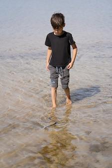 Um menino caminha descalço pela parte rasa para pegar uma cobra que nada na água na frente dele