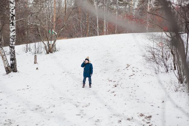 Um menino caminha em uma floresta de inverno ou parque, roupas quentes de neve e esportes de inverno