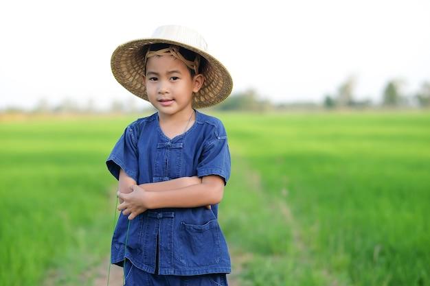 Um menino camponês com uma camisa tradicional e um chapéu de palha está de pé com os braços cruzados e sorrindo no campo.
