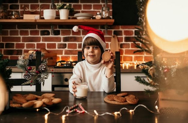 Um menino caucasiano com um suéter de tricô branco e um chapéu de ano novo está sentado a uma mesa com biscoitos de leite e aveia