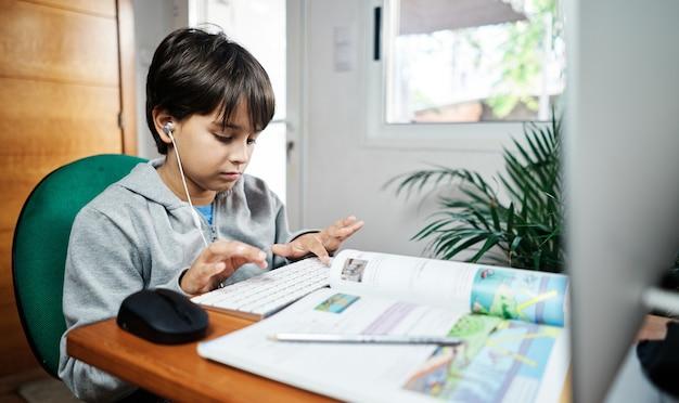 Um menino caucasiano dá aulas em casa por videoconferência. criança confinada em casa por covid-19. novo normal. escola em casa