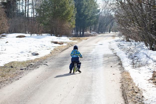 Um menino caucasiano de 2 anos aprende a andar de bicicleta de equilíbrio na estrada na aldeia na primavera, quando a neve ainda não derreteu