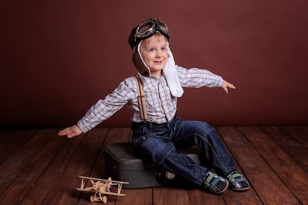 Um menino com capacete de piloto brinca com um avião de madeira. menino em uma camisa xadrez e suspensórios.