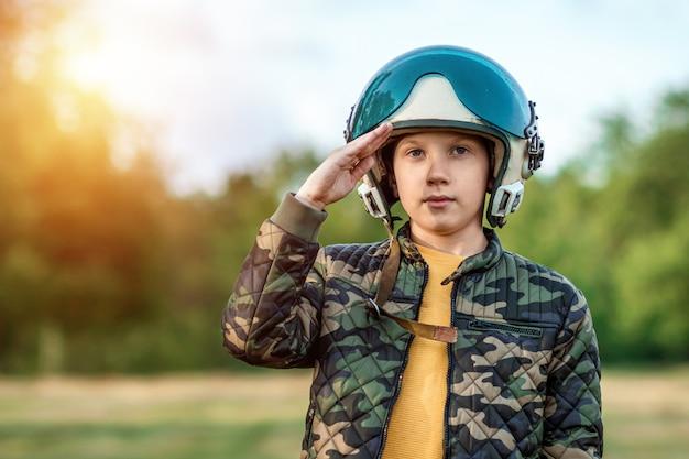 Um menino com capacete de piloto faz uma saudação.