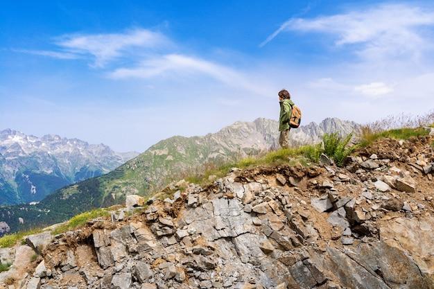 Um menino com mochilas atrás de si em pé no topo da montanha, descansando após uma longa subida. conceito de férias ativas. caminhadas com crianças.