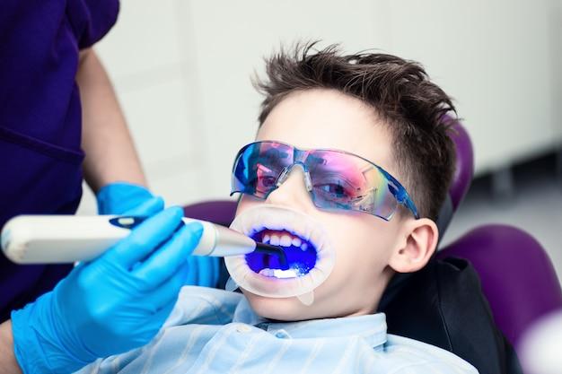 Um menino com óculos de proteção na cadeira odontológica.