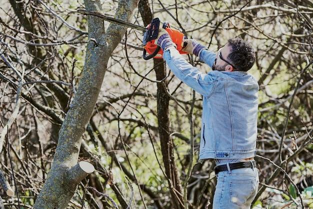 Um menino com óculos de segurança e uma serra elétrica poda uma árvore na floresta.