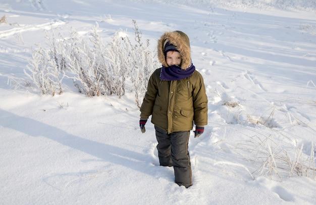 Um menino com roupas quentes caminha no parque de inverno e brinca com a neve