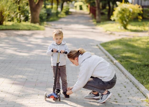 Um menino com sua mãe andando no parque em uma scooter